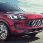 A close up of the front end of a red 2020 Ford Escape.