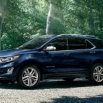 A blue 2020 Chevy Equinox is parked in a driveway with trees behind it.