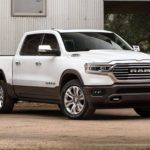 A white 2020 Ram 1500 is parked in front of a metal walled building.