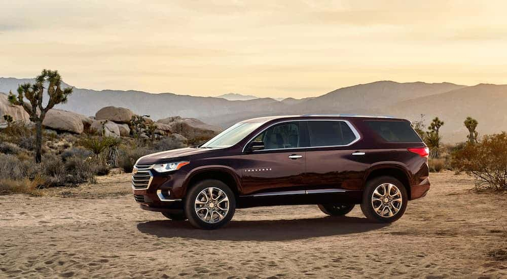A burgundy 2018 Chevy Traverse, which is a popular option among used cars for sale, is parked on a dirt road.