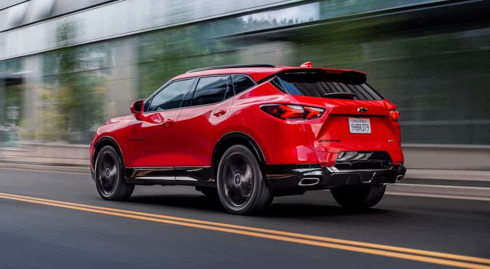 A red 2020 Chevy Blazer RS is driving down a city street.