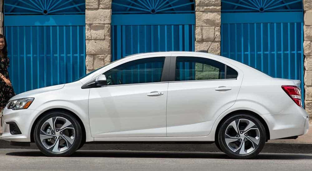 A white 2019 Chevy Sonic is parked on the side of a street next to a concrete building.
