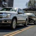 A white 2020 Ford F-150, which wins when comparing the 2020 Ford F-150 vs 2020 Ram 1500 is towing a boat.