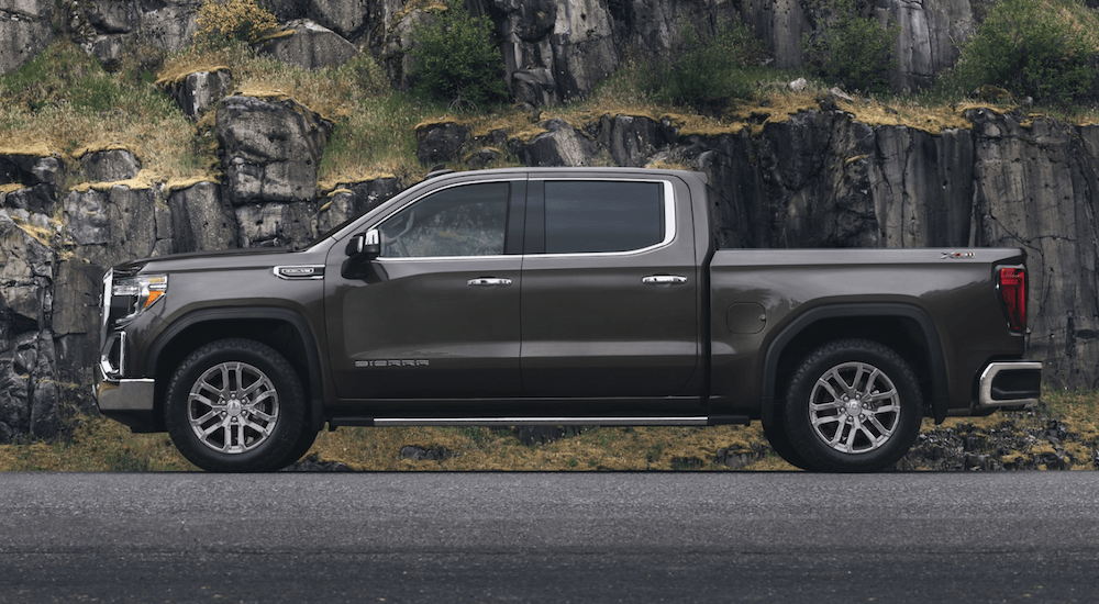 A brown 2020 GMC Sierra 1500 is parked in front of a rock wall.