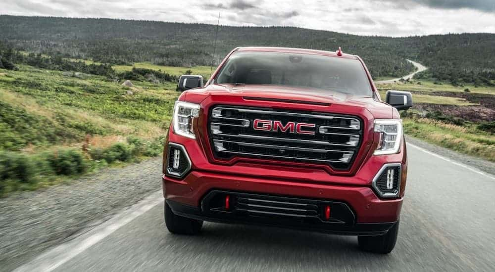 A red 2020 GMC Sierra 1500, which wins when comparing the 2020 GMC Sierra 1500 vs 2020 Nissan Titan, is driving with hills in the distance.