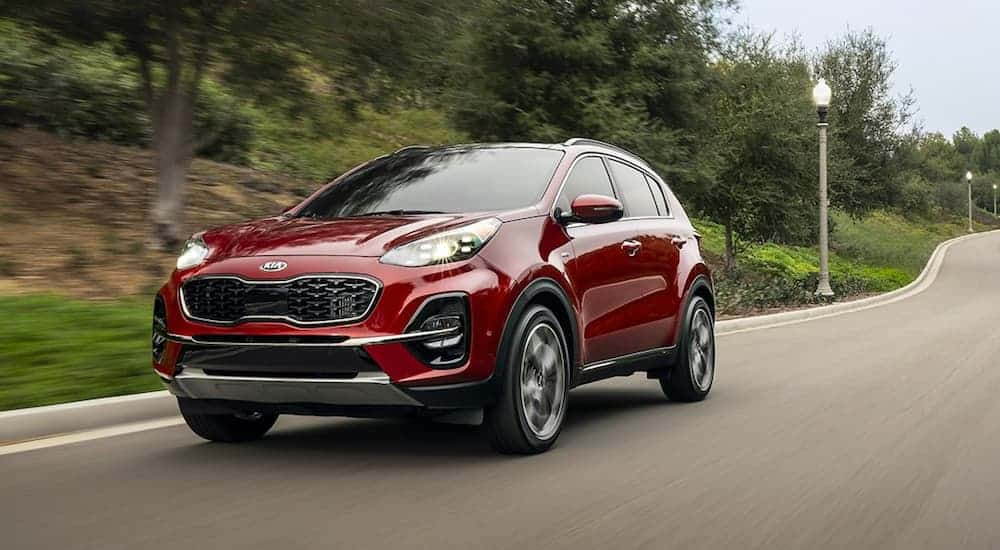 A red 2020 Kia Sportage is driving on a road past blurred trees.