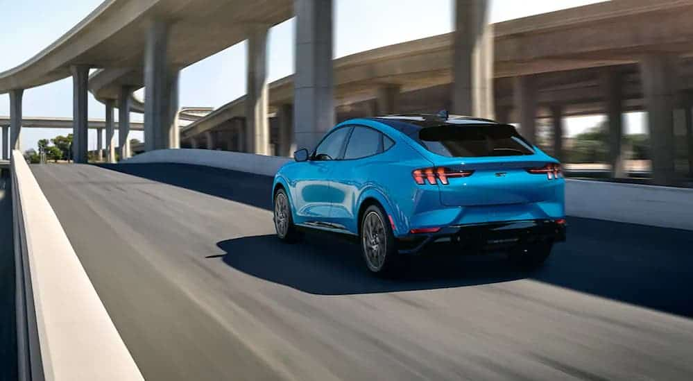 A blue 2021 Ford Mustang Mach-E GT is driving through a city under a highway bridge.