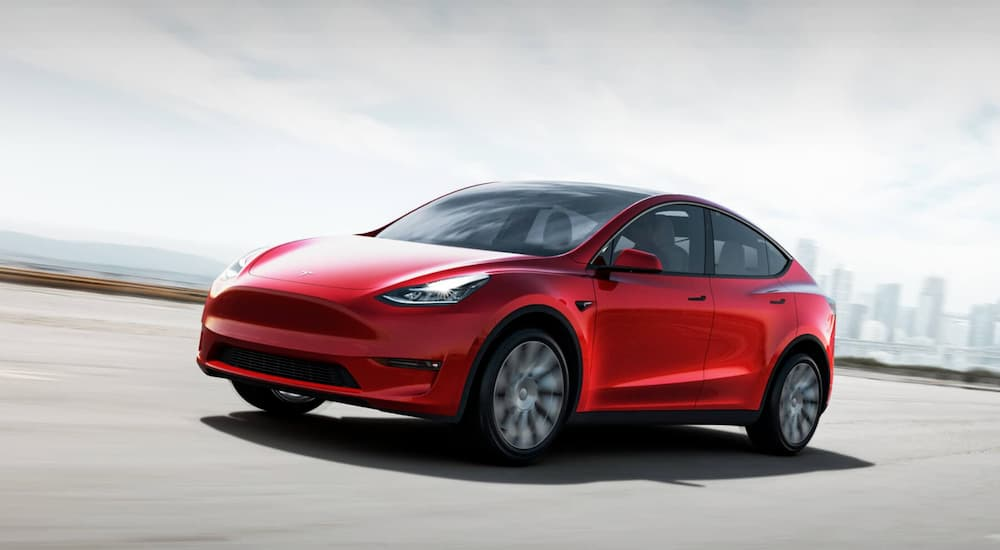 A red Tesla Model Y is driving on a highway.