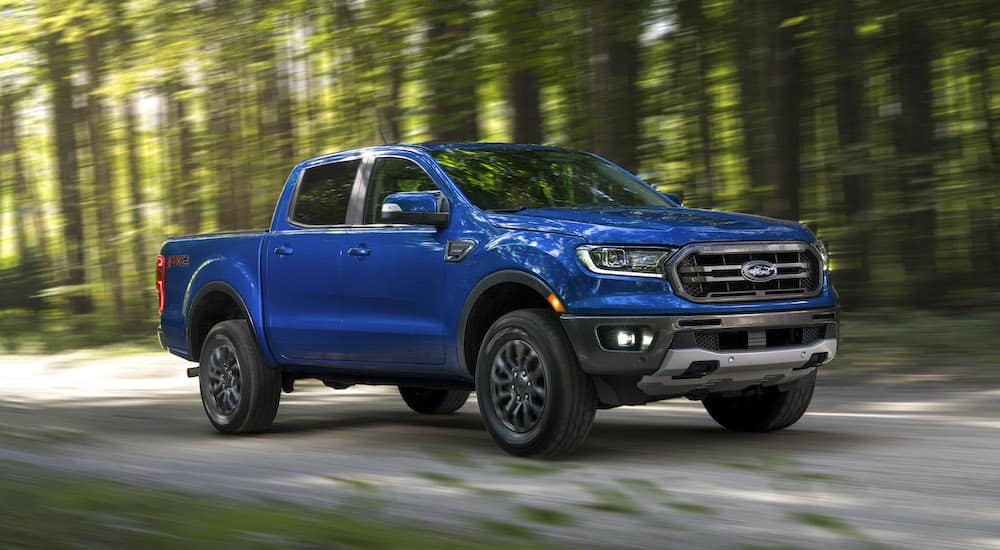 A blue Ford Ranger FX2 driving down a dirt road in a shadowy forest.