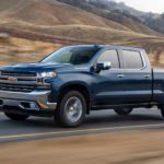 A blue 2020 Chevy Silverado, which wins when comparing the 2020 Chevy Silverado vs 2020 Ford F-150, is driving on a brown grass lined road.