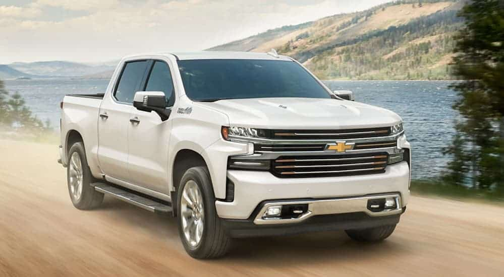 A white 2020 Chevy Silverado 1500 is driving on a dirt road next to a large lake.
