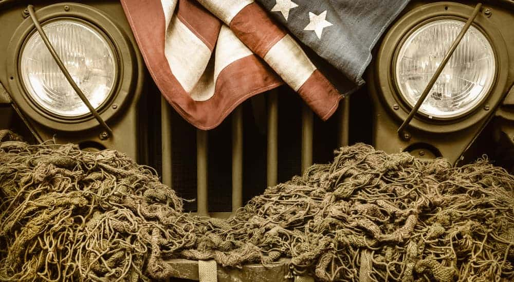 A close of a retro military Jeep grille is shown with a rope and an American flag on it.