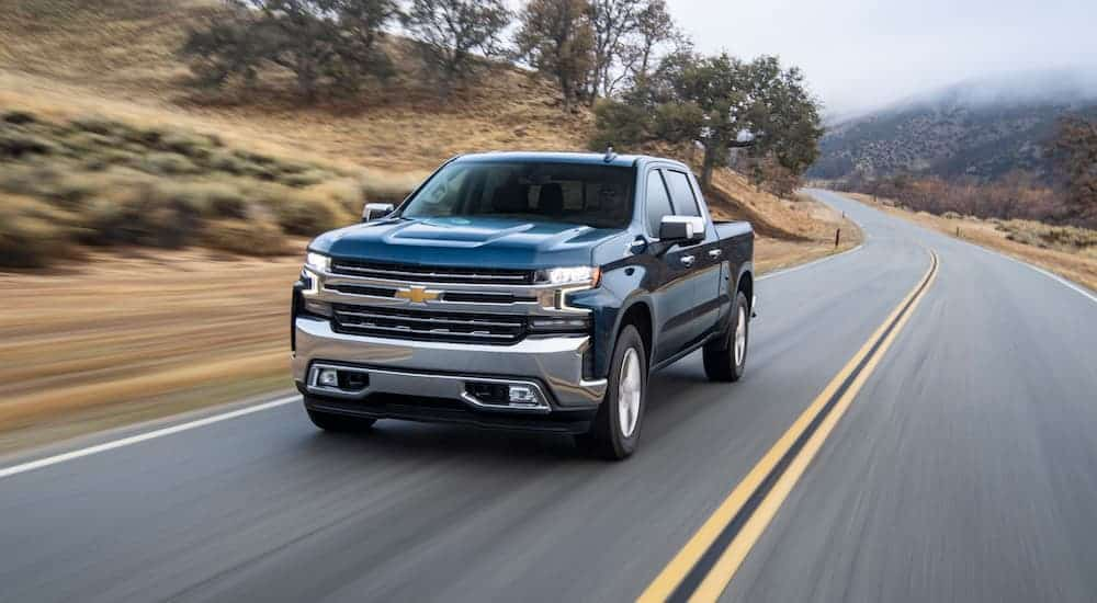A blue 2020 Chevy Silverado 1500 is driving on a tree lined road.