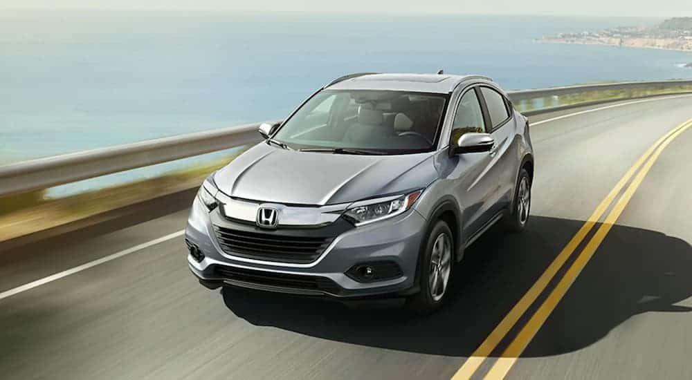 A silver 2020 Honda HR-V is driving along a bay.
