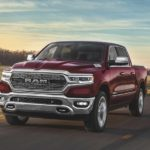 A red 2020 Ram 1500, which wins when comparing the 2020 Ram 1500 vs 2019 Ram 1500, is driving past fields.