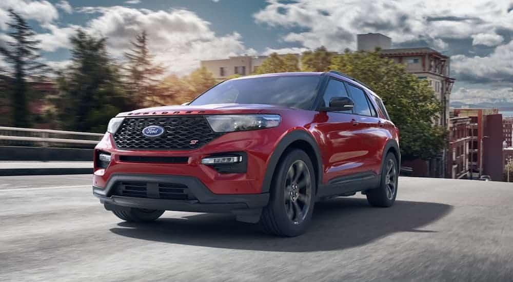 A red 2020 Ford Explorer, which wins when comparing the 2020 Ford Explorer vs 2020 Kia Telluride, is driving on a city street.