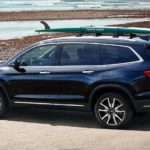 A blue 2020 Honda Pilot is parked at the ocean with a surfboard on the roof rack.