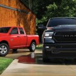 A red 2020 Ram 1500 Classic Express is next to a black 1500 in front of a barn.