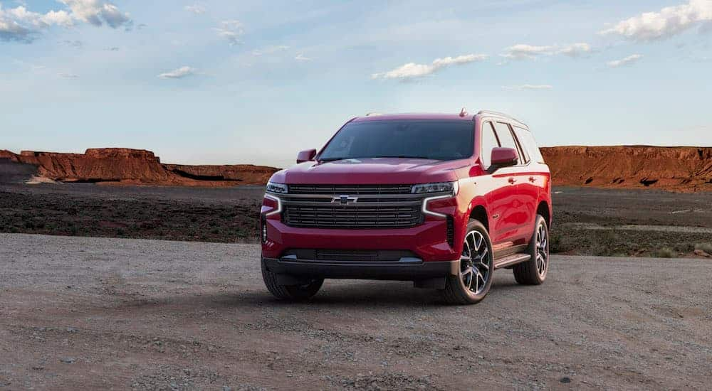 A red 2021 Chevy Tahoe is parked in a parking lot with mountains in the distance.