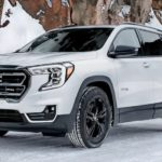 A white 2021 GMC Terrain AT4 is parked on a snowy road.