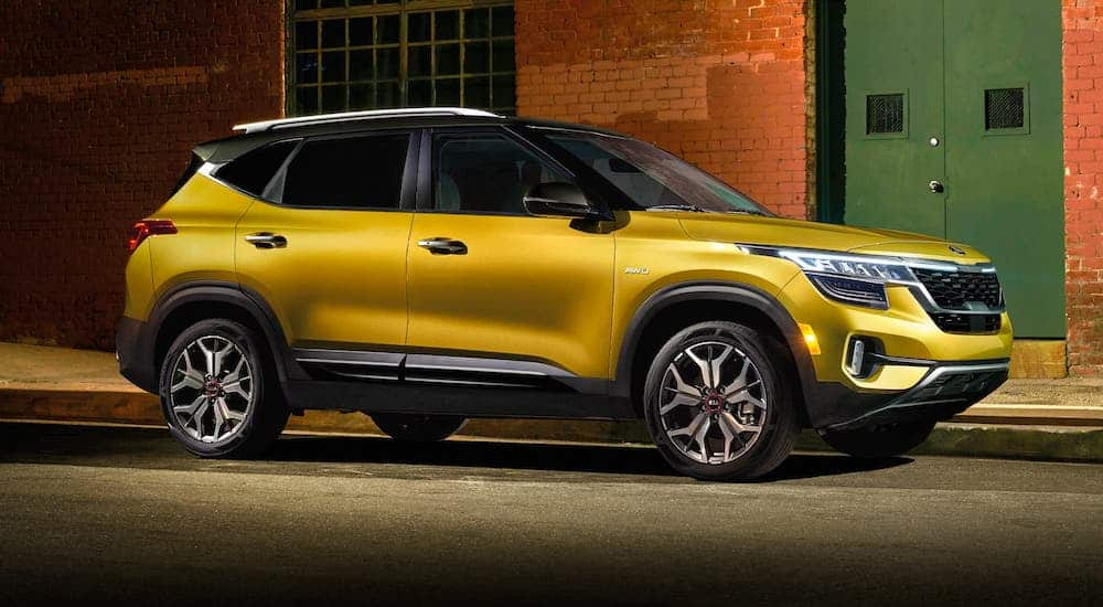 A yellow 2021 Kia Seltos is parked in front of a brick building.