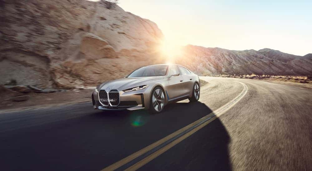 A beige 2021 BMW i4 is driving past a rock face with the sun setting behind it.