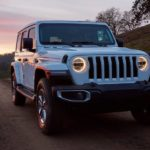 A white 2020 Jeep Wrangler is driving on a rural road at dusk.