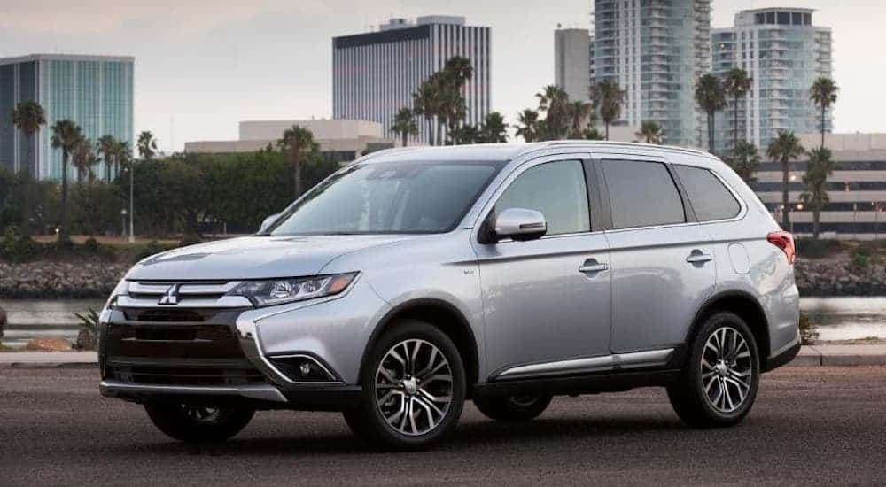 A silver 2017 Mitsubishi Outlander is parked in front of a city sky line.