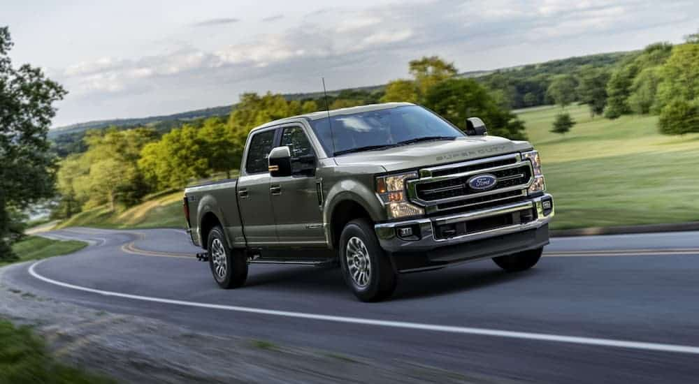 A grey 2020 Ford F-250 is driving on a winding road.