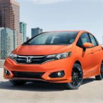 An orange 2020 Honda Fit is parked on a rooftop parking garage with city buildings behind it.