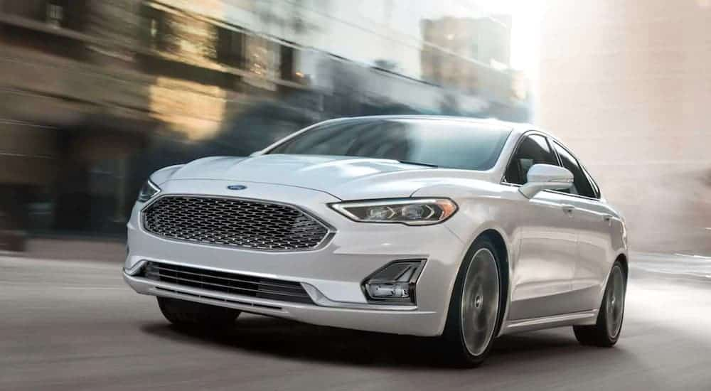 A white 2020 Ford Fusion is driving down a city street.