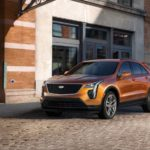 An orange 2020 Cadillac XT4 is parked under a bridge on a cobblestone road.