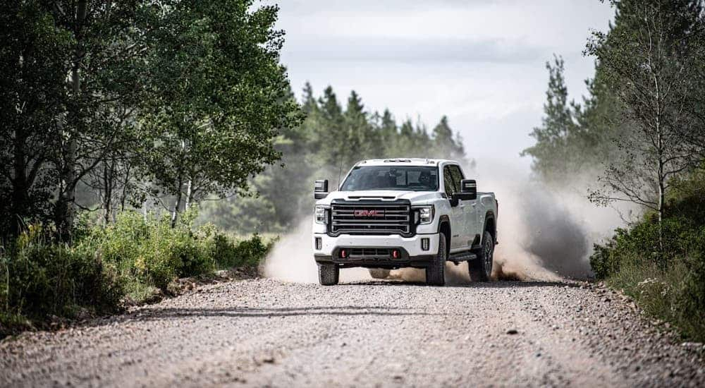 A white 2020 GMC Sierra 2500HD AT4 is kicking up dirt on a dirt road.