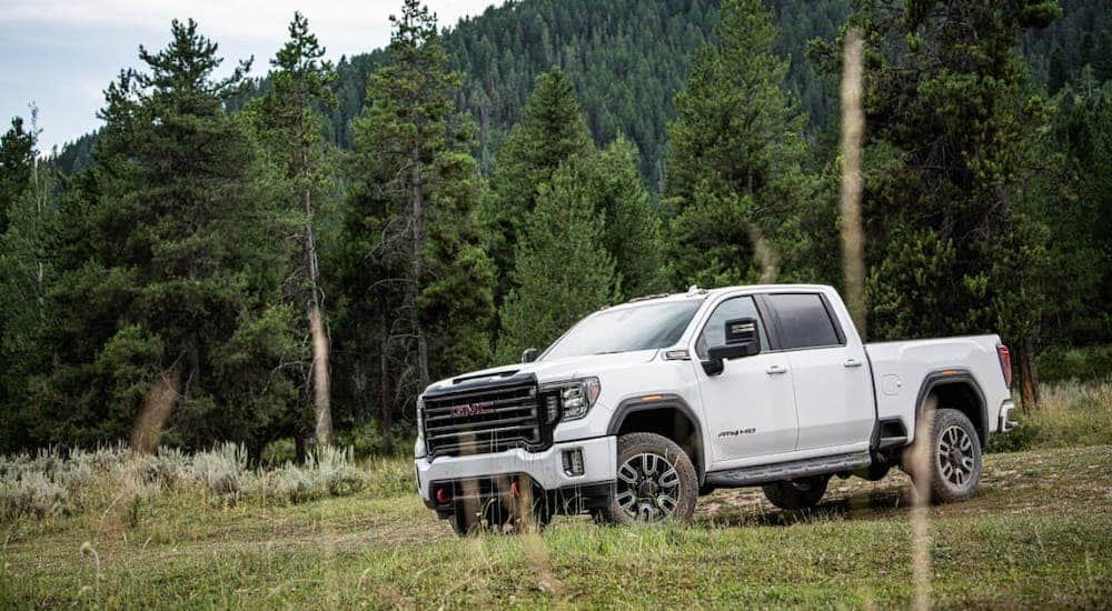 A white 2020 GMC Sierra 2500HD AT4 is parked in front of trees and a mountain.