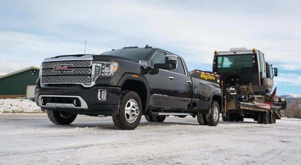 A low angle is shown of a black 2020 GMC Sierra 3500HD Denali that is towing construction equipment.