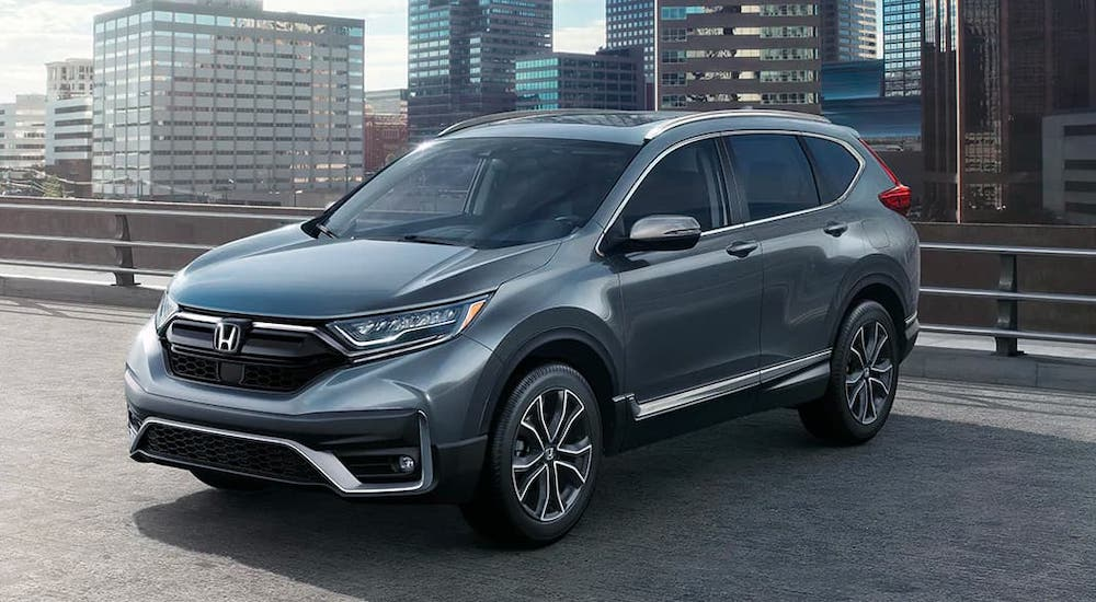 A gray 2020 Honda CR-V Touring is parked atop a parking garage. Check one out at a Honda Dealer Near Me.