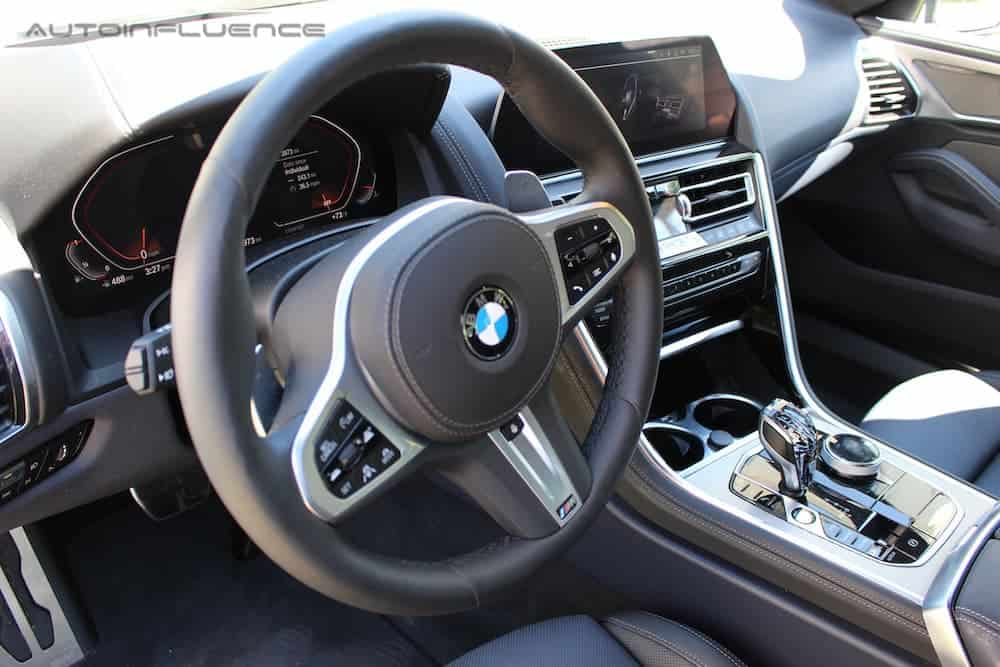 The wheel and infotainment features in a 2020 BMW 840i Gran Coupe are shown.