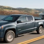 A grey 2020 Chevy Colorado LT is towing a boat past a lake after winning the 2020 Chevy Colorado vs 2020 Ford Ranger comparison.