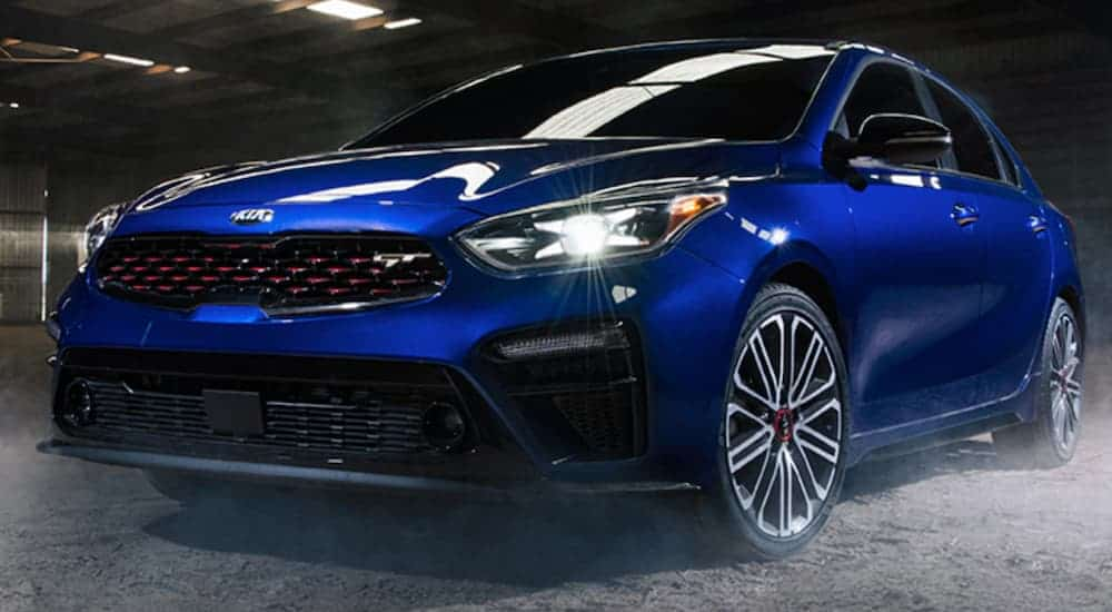 A blue 2020 Kia Forte is parked in a warehouse with a dirt floor.