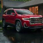 A red 2020 GMC Acadia is parked in front of a modern house.