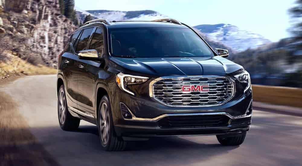 A black 2020 GMC Terrain is driving on a mountain road and is popular among GMC SUVs.