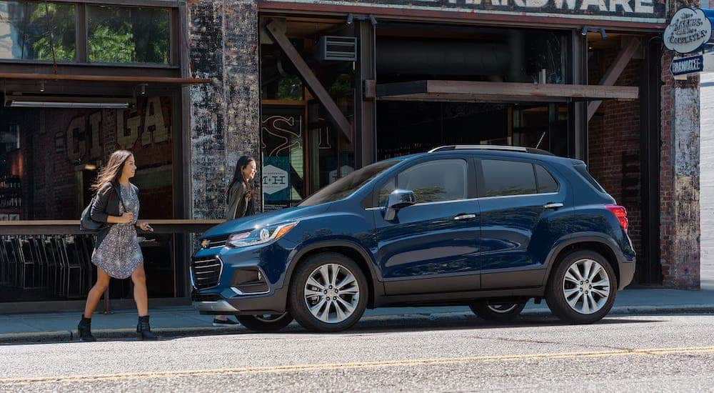 Two women are walking towards a blue 2020 Chevy Trax which is parked on a city street.