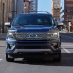 A blue 2020 Ford Expedition Platinum is shown from the front driving on a city street.