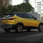 One of the new Kia models for the year, a yellow 2021 Kia Seltos, is parked in a city.