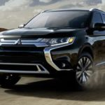 A 2019 Mitsubishi Outlander is driving around a corner in front of hills.