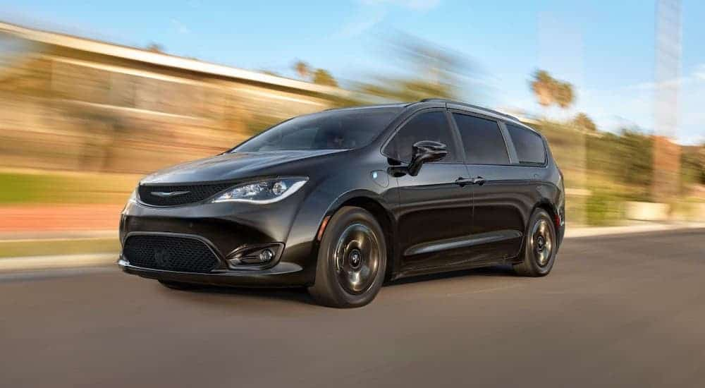 A black 2020 Chrysler Pacifica is driving on a road with a blurry background.