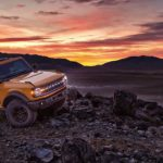A yellow 2021 Ford Bronco 2 door is parked on rocks in front of mountains and a vibrant orange sunset.