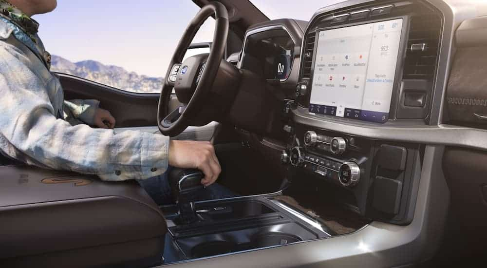 The screen in a 2021 Ford F-150 is shown with a person in the driver's seat.