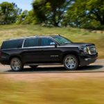 A popular Chevy SUV, a black 2020 Chevy Suburban, is driving on a rural highway and shown from the side.
