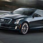 A black used Cadillac for sale, a 2019 Cadillac ATS, is driving on a blurry city street.